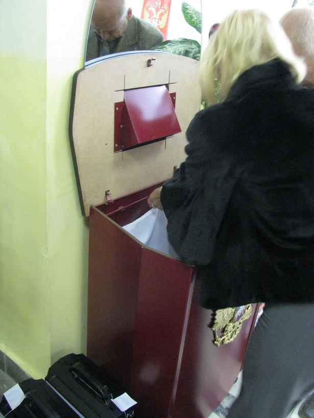 Председатель демонстирирует пустой стационарный ящик для голосования